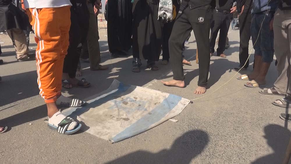 Shia muslims trampled and then burned the Israeli flag to show their solidarity for the Palestinian people who are treated unfairly by Israel. Photo: AMCnews